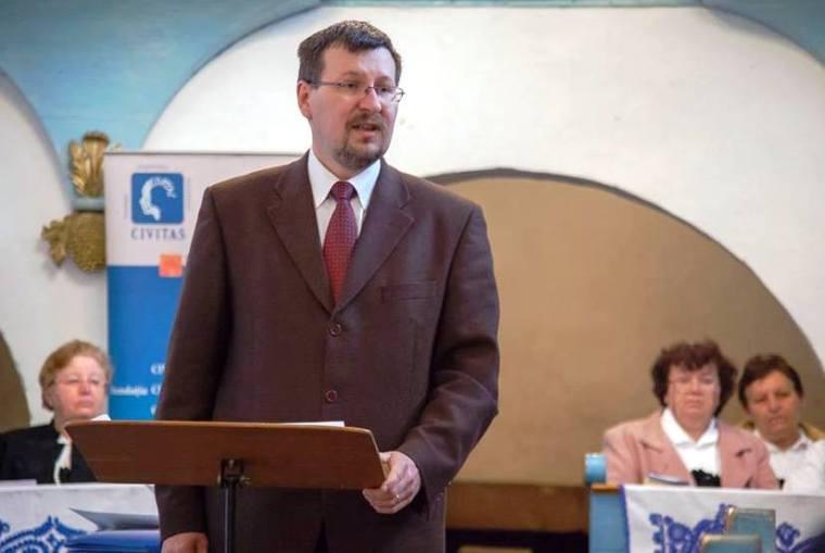 Demeter Sándor Lóránd unitárius tiszteletes bejelenti, hogy magyar, német és román nyelven zajlik majd a sajtókonferencia - szinkrontolmácsok segítségével hidalják át a nyelvi akadályokat
